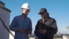 Två unga manliga arkitekter eller teknikerer stock video