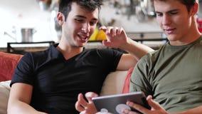 Två unga manliga vänner som använder minnestavladatoren stock video