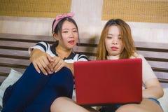 Två unga nätta och lyckliga asiatiska koreanska hemmastadda sovrum för studentflickor tillsammans genom att använda socialt massm royaltyfria foton