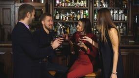 Två unga par i klubban eller stången som har gyckel som rostar vinexponeringsglas arkivfilmer