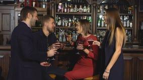 Två unga par i klubban eller stången som har gyckel som rostar vinexponeringsglas lager videofilmer