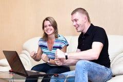 Två unga personer som leker i lekar på bärbar dator. Arkivbild