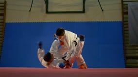Två unga pojkar som öva sparkboxning på idrottshallen i ultrarapid arkivfilmer