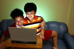 Två unga pojkar som använder en dator och le för bärbar dator Arkivfoto