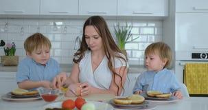 Två unga pojkar som barn hjälper mamman i köket, förbereder hamburgare som skivar grönsaker ost och korvar lager videofilmer
