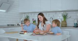 Två unga pojkar som barn hjälper mamman i köket, förbereder hamburgare som skivar grönsaker ost och korvar stock video