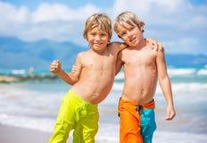 Två unga pojkar som har gyckel på den tropcial stranden Arkivbilder