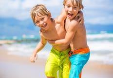 Två unga pojkar som har gyckel på den tropcial stranden Arkivfoton