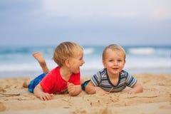 Två unga pojkar som har gyckel på en strand, lyckligt skratta för vänner Arkivfoton
