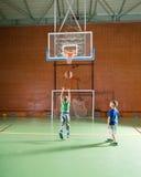 Två unga pojkar som spelar basket tillsammans Arkivfoton