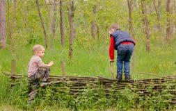 Två unga pojkar som spelar på ett lantligt staket Fotografering för Bildbyråer