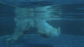 Två unga sexiga flickor som hoppar i lyxigt pölvatten på solig dag stock video