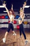 Två unga skratta konditionkvinnor som hoppar i idrottshall Royaltyfria Bilder