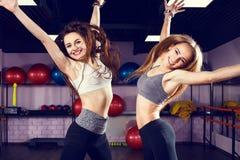 Två unga skratta konditionkvinnor som hoppar i idrottshall Royaltyfri Bild