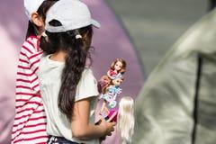 Två unga små flickor som rymmer och spelar med deras plast- dockor arkivfoto