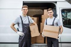 Två unga stiliga le arbetare som bär likformig, står bredvid skåpbilen mycket av askar Husflyttning, flyttkarl royaltyfria foton