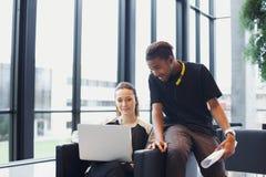 Två unga studenter som använder bärbara datorn i universitetsområde Arkivfoton
