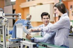 Två unga studenter som tillsammans arbetar på ett projekt i labb Arkivbild