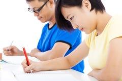 Två unga studenter som tillsammans lär i klassrum royaltyfri bild