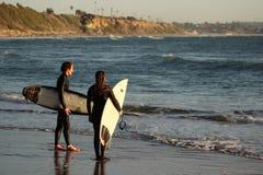 Två unga surfare på Swami` s sätter på land i Encinitas Kalifornien royaltyfri bild