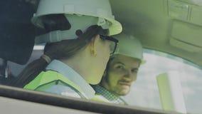 Två unga teknikerer en man och en kvinna i gröna västar och hjälmar stock video
