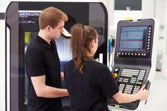 Två unga teknikerer som fungerar CNC-maskineri på fabriksgolv Arkivbild