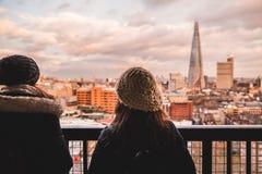 Två unga turist- kvinnliga vänner som ser den moderna London skylinen Arkivfoto