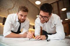Två unga upphetsade affärsmän som arbetar på ett affärsplan royaltyfria foton