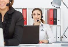 Två unga vänliga kvinnor med i den tillfälliga dräkten för affär genom att använda hörlurar med mikrofon arkivfoton