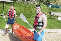 Två unga vänner som går i havet med den orange kanoten arkivfoton