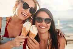 Två unga vänner som har glass utanför Arkivfoton