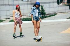 Två unga vuxna flickor som rider på gatan Arkivfoto