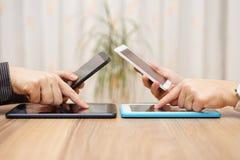 Två unga vuxna människor använder åtskilliga minnestavlor och telefoner i deras Royaltyfri Foto