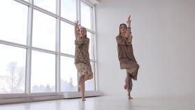 Två unga yogakvinnor som öva örnen, poserar tillsammans framme av änkorna arkivfilmer