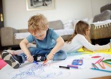 Två ungar är spela och dra på golvet arkivbild