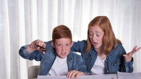 Två ungar förargas som gör deras läxa Royaltyfria Foton