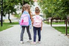 Två ungar går till skolan med ryggsäckar Begreppet av skolan, studie, utbildning, kamratskap, barndom royaltyfri foto