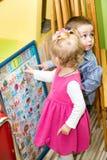 Två ungar i Montessori förskole- grupp pojkeflicka little som leker arkivfoto