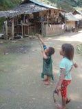 Två ungar i nordliga Thailand spelar med deras katapult royaltyfri fotografi