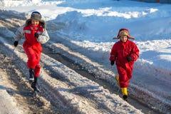 Två ungar i rainboots som kör på ispölen royaltyfri foto