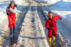 Två ungar i rainboots som kör på ispölen arkivfoton