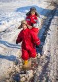 Två ungar i rainboots som kör på ispölen fotografering för bildbyråer
