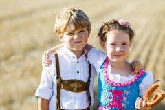 Två ungar i traditionella bayerska dräkter i vetefält Tyska barn som äter bröd och kringlan under Oktoberfest arkivbilder