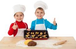 Två ungar med bakning och det ok tecknet Royaltyfria Bilder