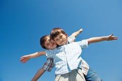 Två ungar med deras beväpnar öppen sned boll Royaltyfri Foto