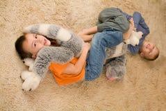 Två ungar med en toy på golvet Arkivbilder