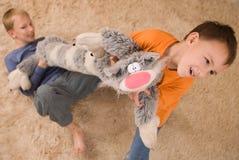 Två ungar med en toy på golvet Royaltyfri Fotografi
