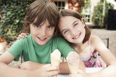 Två ungar med glasskottar på den utomhus- tabellen Royaltyfri Fotografi