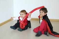 Två ungar med vampyren kostymerar enyoing i ett parti arkivbild
