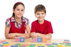 Två ungar på tabellen med pusselbokstäver Arkivfoton